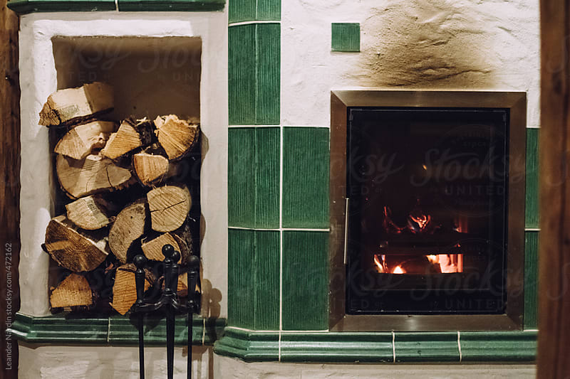 masonry heater with logs and fireplace by Leander Nardin for Stocksy United