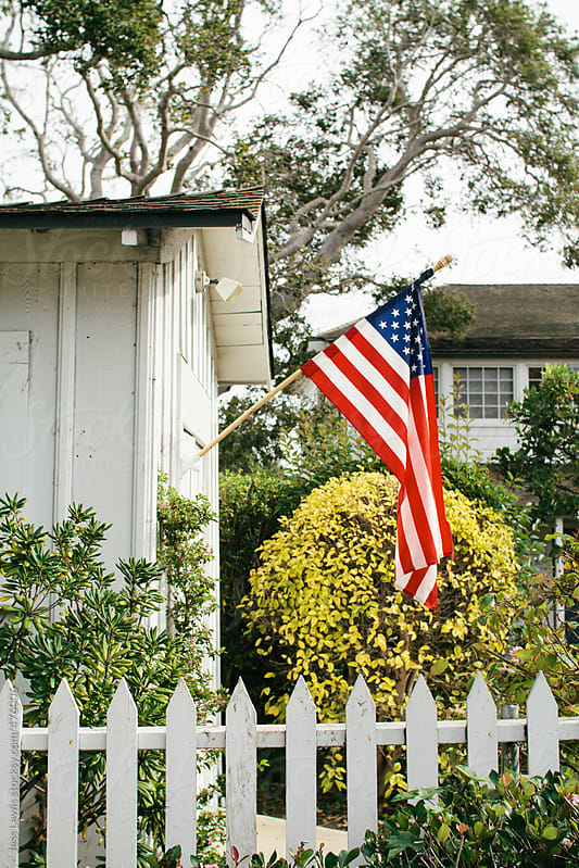united states flag on garage exterior by Jess Lewis for Stocksy United