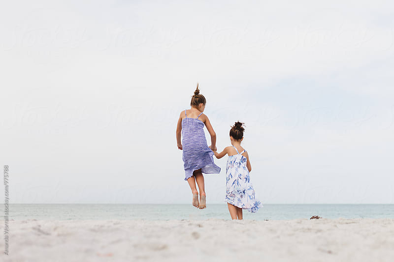 Two girls jumping in sand at the beach while holding hands by Amanda Worrall for Stocksy United