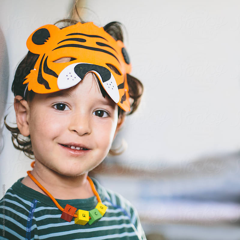 Portrait of a child with tiger mask by michela ravasio for Stocksy United