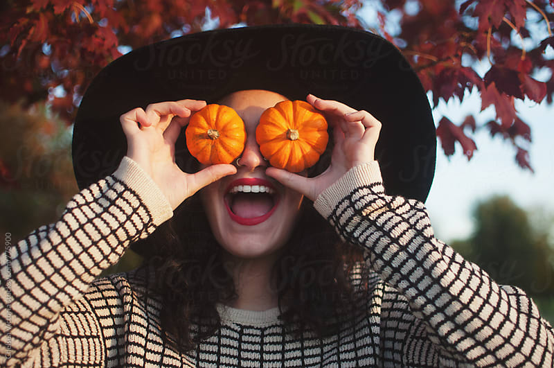 A young man with small pumpkins over his eye making a funny face by Chelsea Victoria for Stocksy United