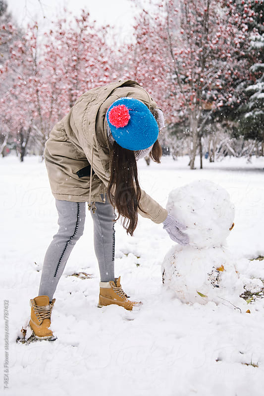 Unrecognizable young woman making snowman by T-REX & Flower for Stocksy United