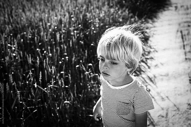 Black and white close up of blonde child in a wheat field. by Julia Forsman for Stocksy United
