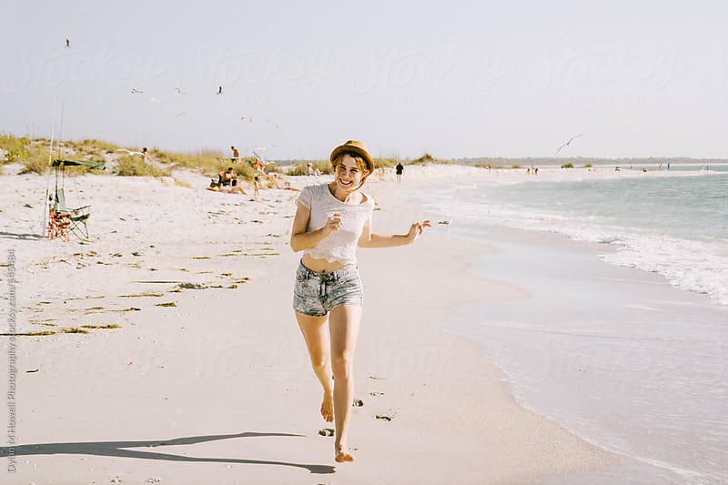 Girl running on the beach by Dylan M Howell Photography for Stocksy United