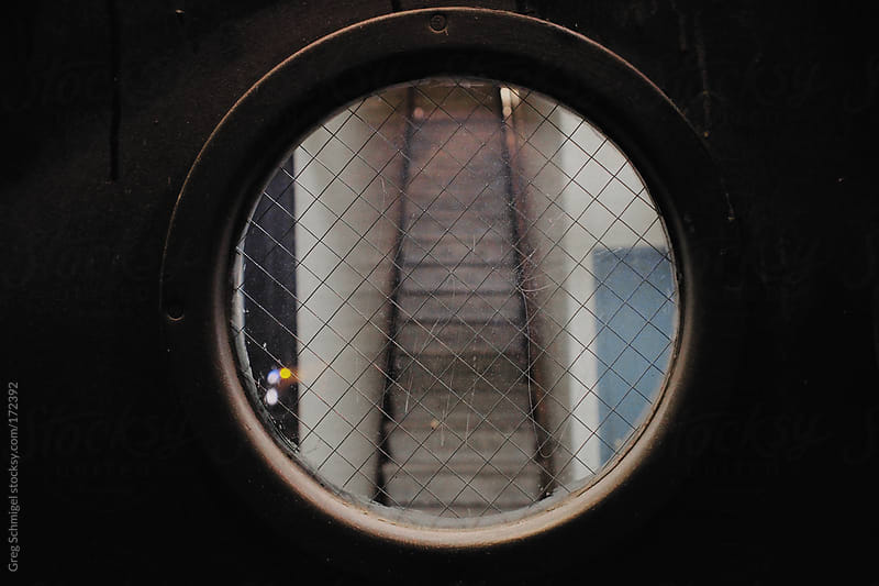 An abstract stairwell seen through a circular window with wires. by Greg Schmigel for Stocksy United
