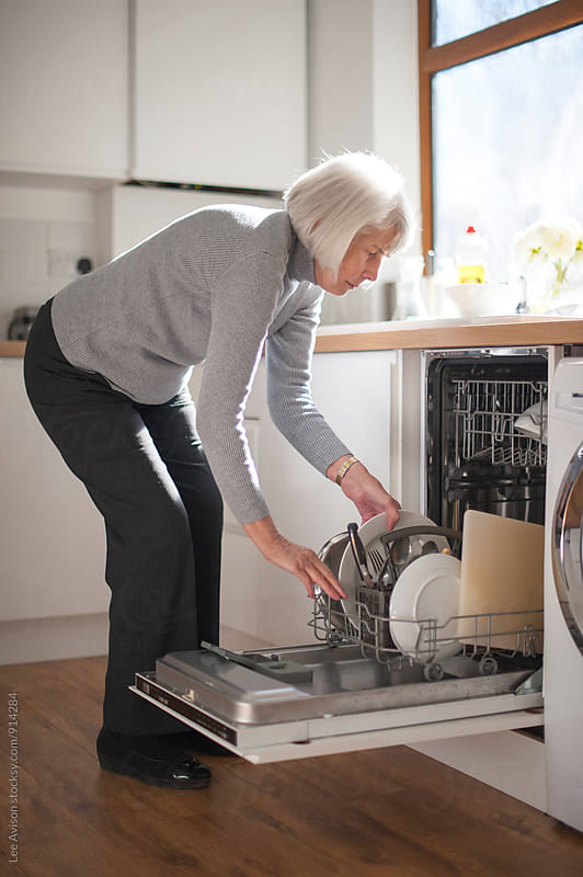 senior woman filling or emptying a dishwasher  by Lee Avison for Stocksy United
