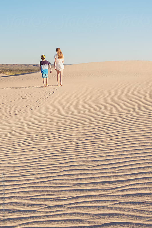Two children walking together across an expanse of wind rippled sand dune by Angela Lumsden for Stocksy United