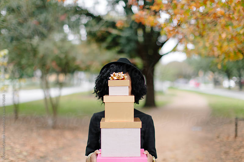 A woman holding a stack of presents  by Kristen Curette Hines for Stocksy United
