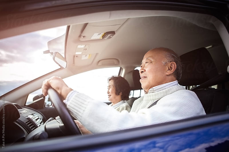 Traveling senior Asian couple driving and riding in a car by Suprijono Suharjoto for Stocksy United