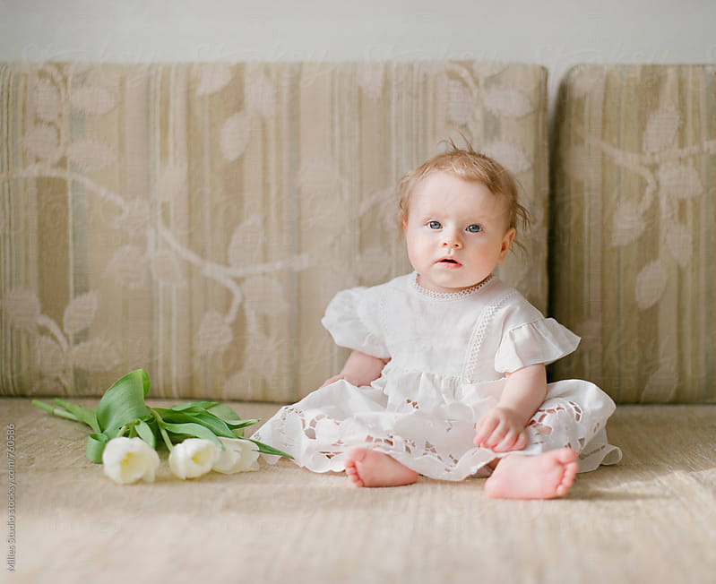 Baby girl sitting on sofa by Milles Studio for Stocksy United