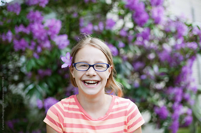 Laughing girl with flower in her hair by Carleton Photography for Stocksy United