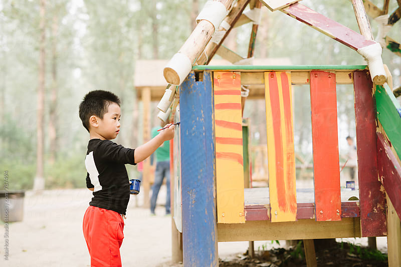 Toddler boy painting outdoors by Maa Hoo for Stocksy United