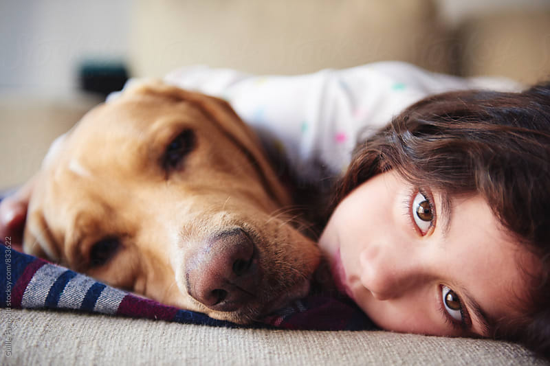 Lovely gold labrador and little girl lying on sofa by Guille Faingold for Stocksy United