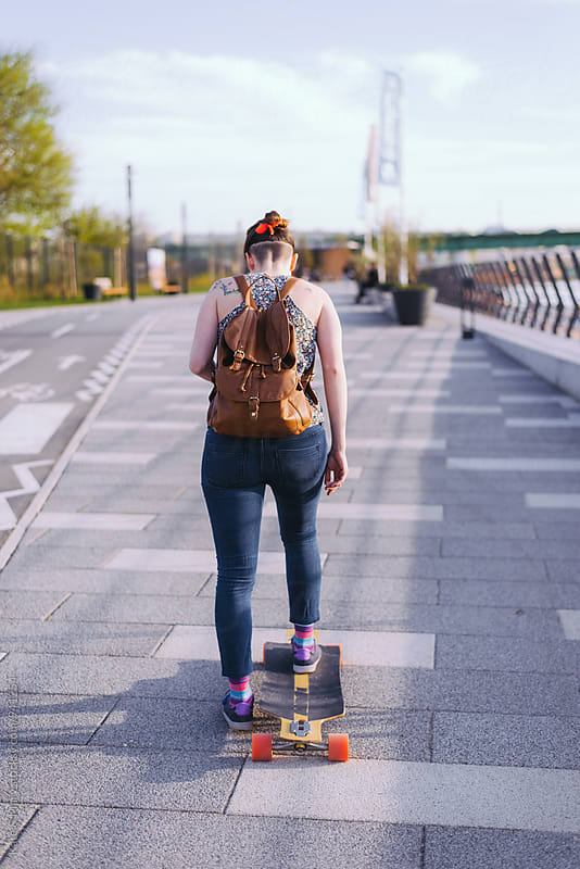 Young woman driving a longboard by Kate & Mary for Stocksy United