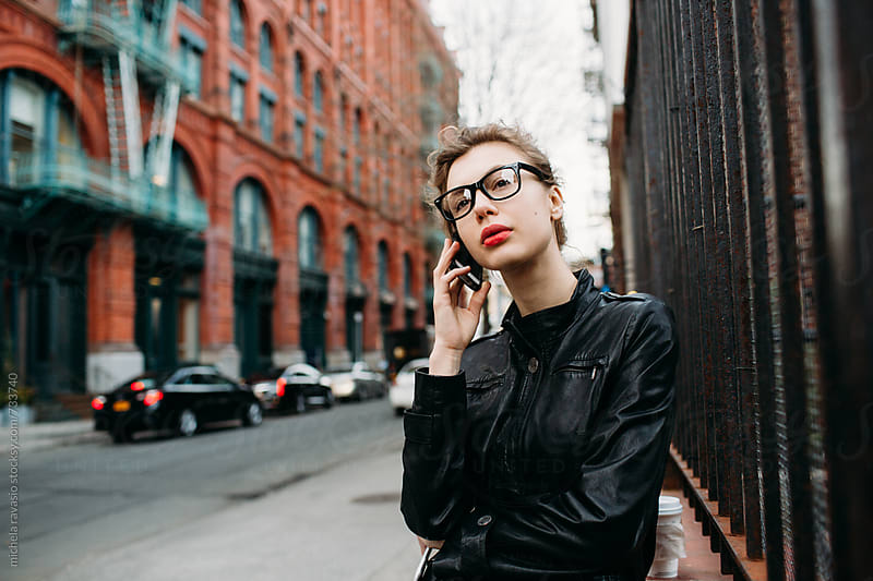 Attractive young woman on her cell phone by michela ravasio for Stocksy United