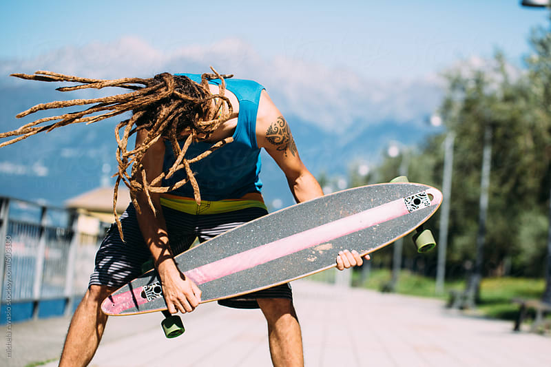 Young man with dreadlocks playing his skateboard by michela ravasio for Stocksy United
