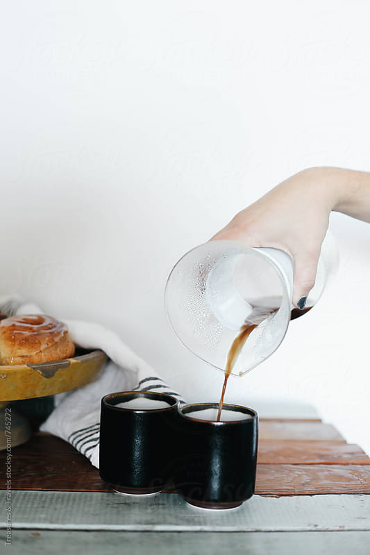 hand pouring coffee into cup by Treasures & Travels for Stocksy United