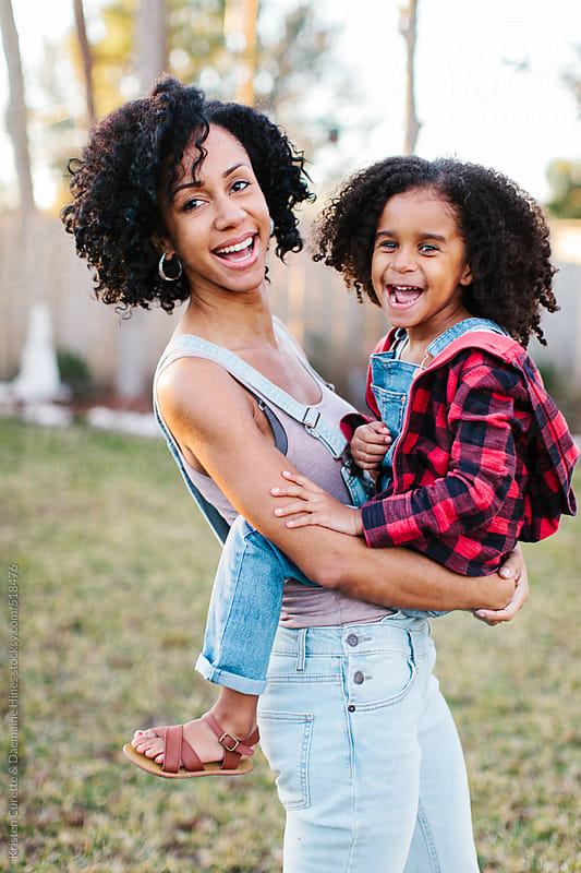 A candid portrait of a hugging mother and daughter by Kristen Curette Hines for Stocksy United