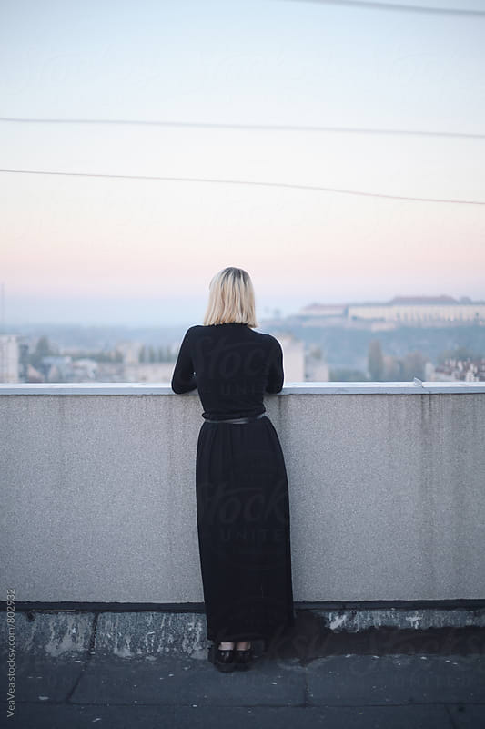 Stylish blonde woman standing on the roof of the building during sunset. From behind. by Marija Mandic for Stocksy United