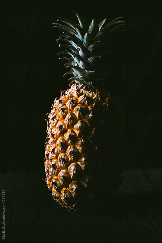 One pineapple on simple black background by Marija Savic for Stocksy United