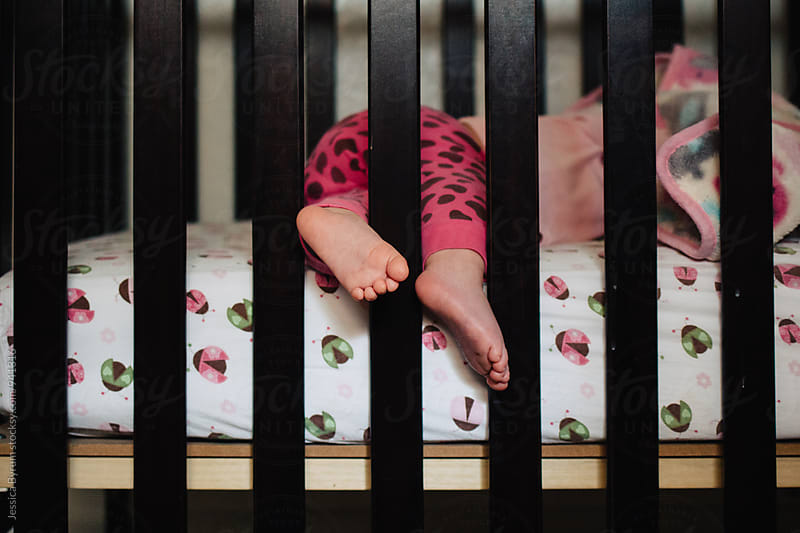 Toddler feet hanging out of crib at nap time by Jessica Byrum for Stocksy United