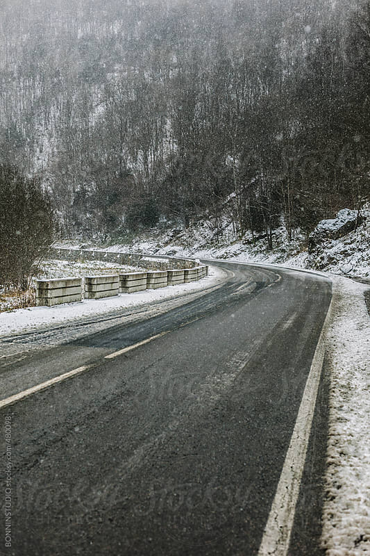 Snowing in winter road.  by BONNINSTUDIO for Stocksy United