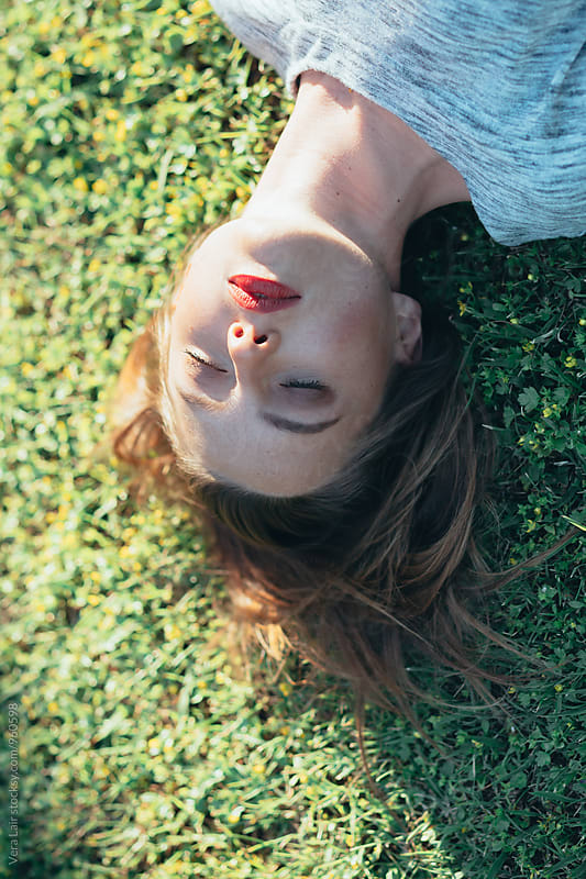 Young woman laying on grass by Vera Lair for Stocksy United