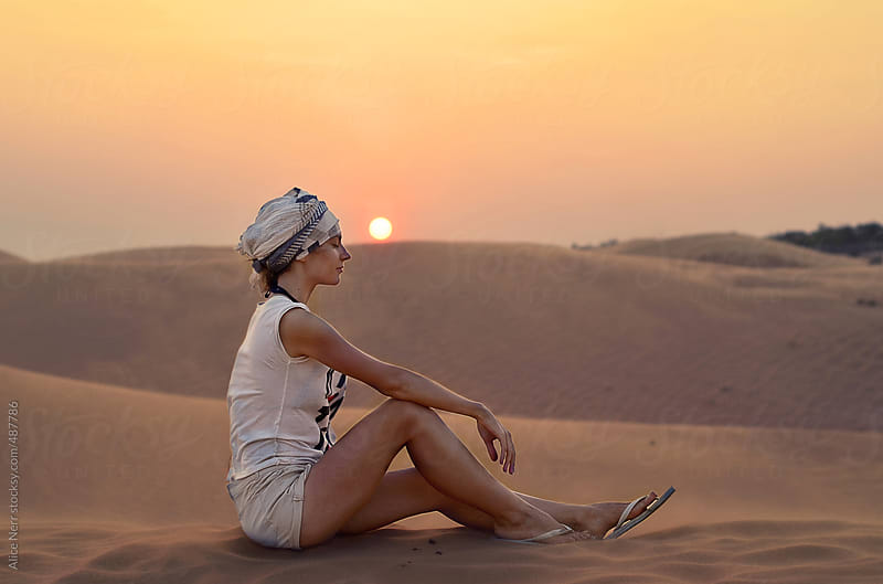 Young beautiful lady sitting at the sand dune during sunset - moment of truth  by Alice Nerr for Stocksy United
