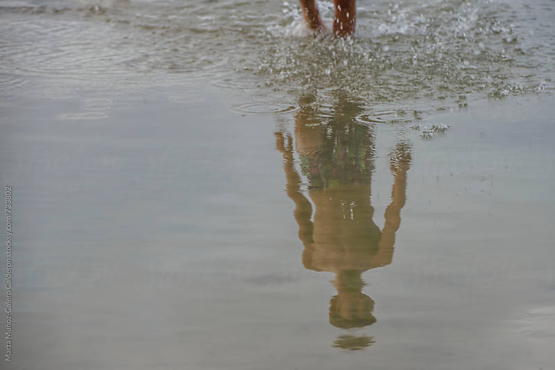 Reflection of a child in the sea by Marta Muñoz-Calero Calderon for Stocksy United