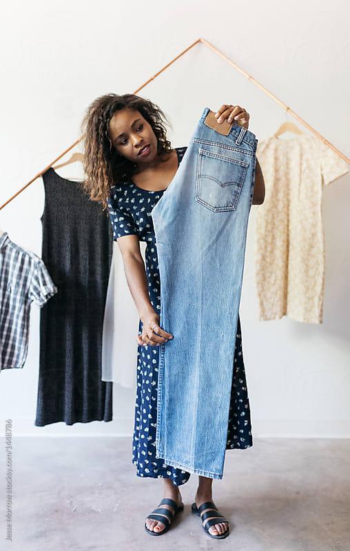 young female fashion entrepreneur holding vintage clothing. Black Bedroom Furniture Sets. Home Design Ideas