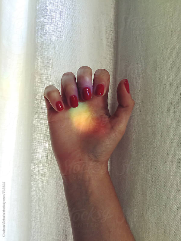 A hand with a rainbow on it by Chelsea Victoria for Stocksy United
