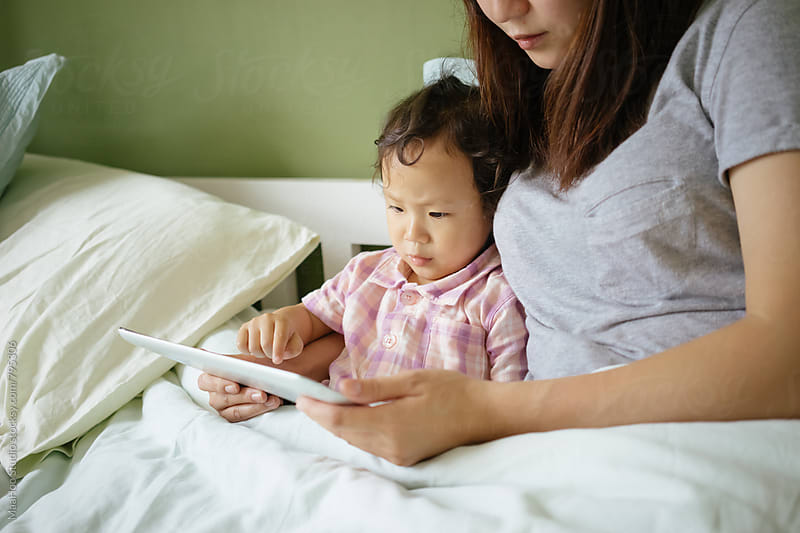 Toddler girl using digital PC with her mother on bed by Maa Hoo for Stocksy United