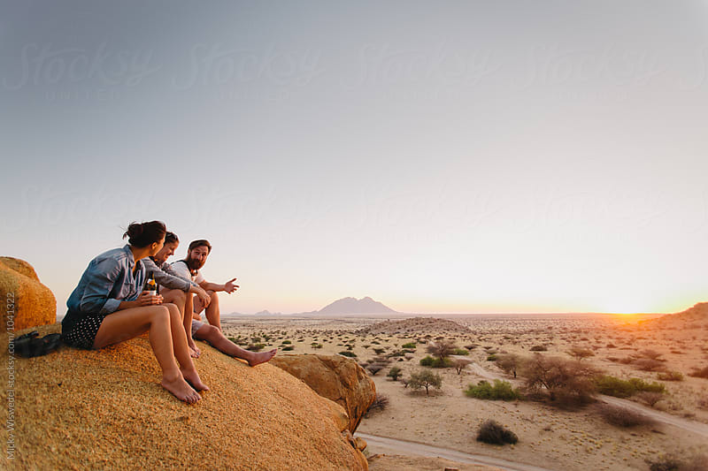 Friends having a good time and drinks at sunset on a boulder in the desert whilst camping by Micky Wiswedel for Stocksy United