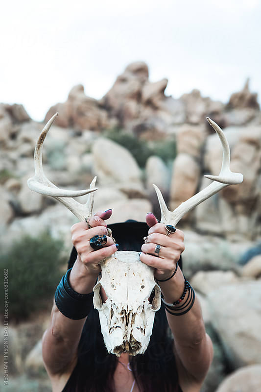 Woman Holding Deer Skull in Front of Face by Meg Pinsonneault for Stocksy United