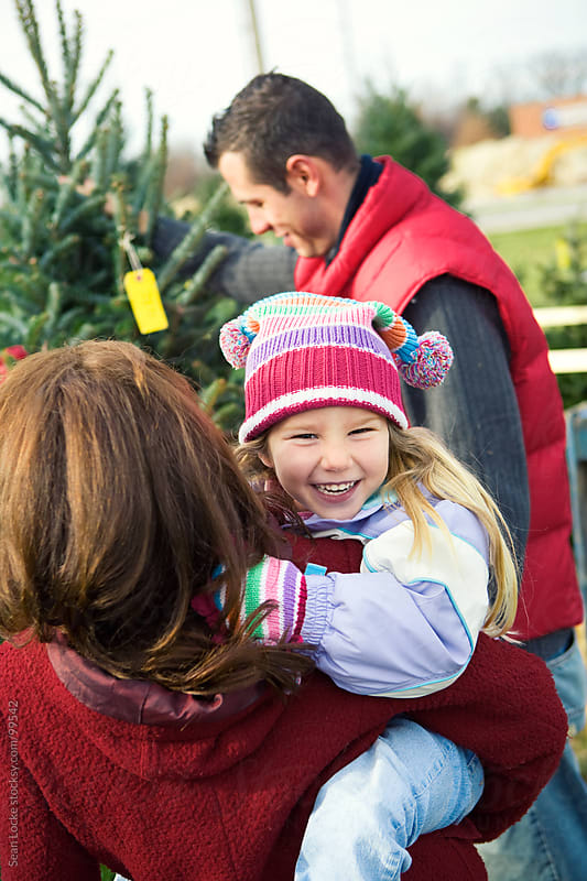 Tree Lot: Little Girl Laughing While Looking For Christmas Tree by Sean Locke for Stocksy United