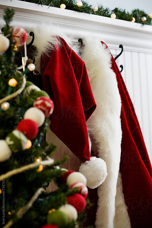 Christmas: Santa Suit Hanging On Wall Behind Christmas Tree by Sean Locke for Stocksy United