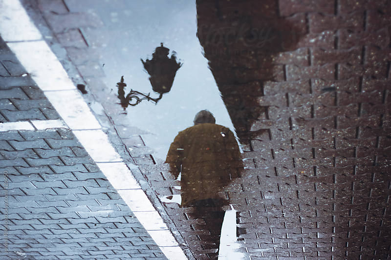 Silhouette puddle reflection of person walking by Jovana Rikalo for Stocksy United