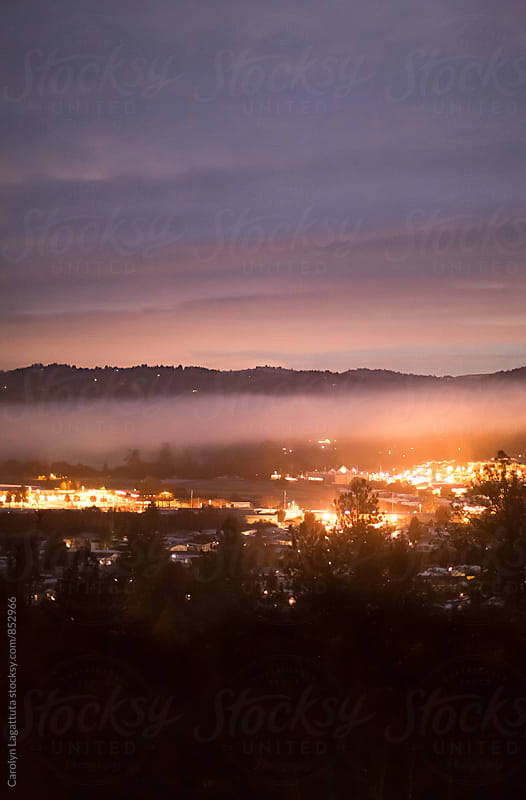Fog blanketing a small town valley by Carolyn Lagattuta for Stocksy United
