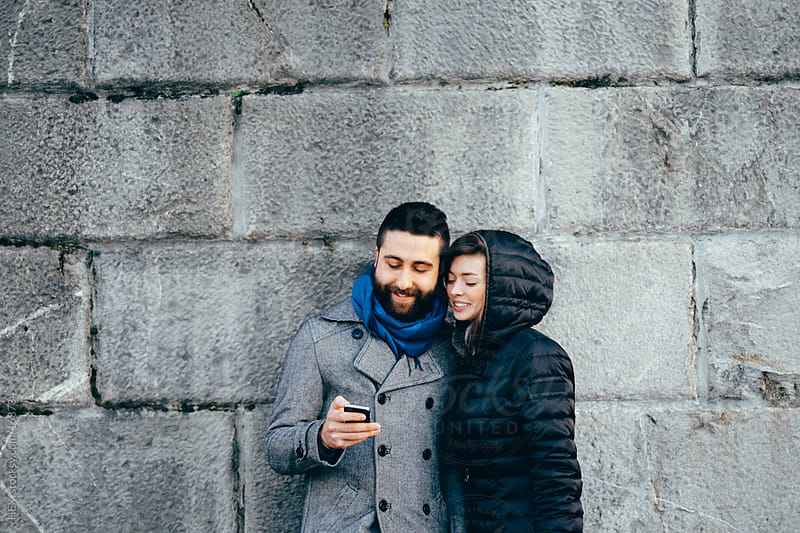 Young Couple with Mobile Phone in front of a Wall by HEX. for Stocksy United