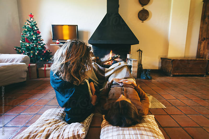 Back view of a couple resting by the fireplace on winter. by BONNINSTUDIO for Stocksy United