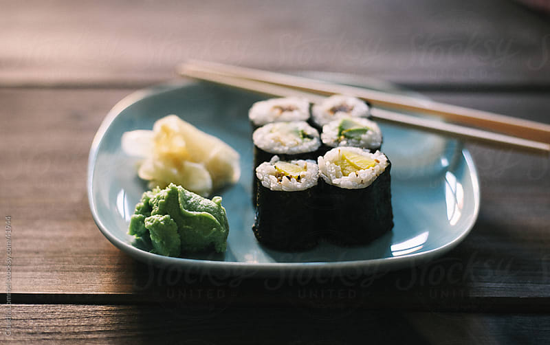 Some Sushi Maki Rolls presented on a Pale Blue Plate along with Wasabi, Ginger and Chopsticks by Claudia Lommel for Stocksy United