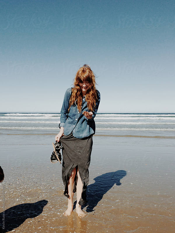 Happy Woman Looking at Shells on the Beach by Kevin Russ for Stocksy United