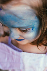 Child Climbing A Tree With Blue Face Paint | Stocksy United