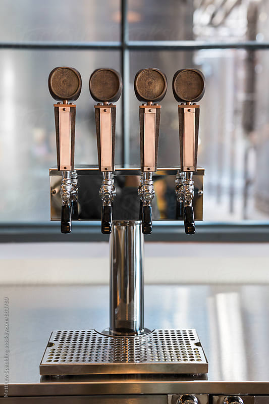 Beer taps for selection at brewery bar by Matthew Spaulding for Stocksy United