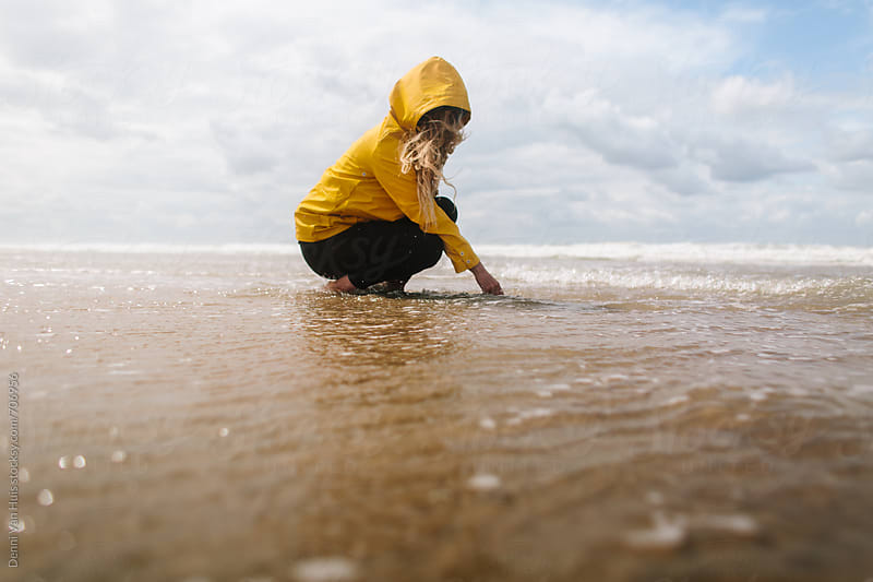 Woman touches the ocean wearing a yellow raincoat by Denni Van Huis for Stocksy United