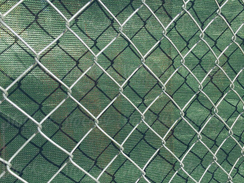 Detail of chain link fence and green fabric at construction site by Paul Edmondson for Stocksy United