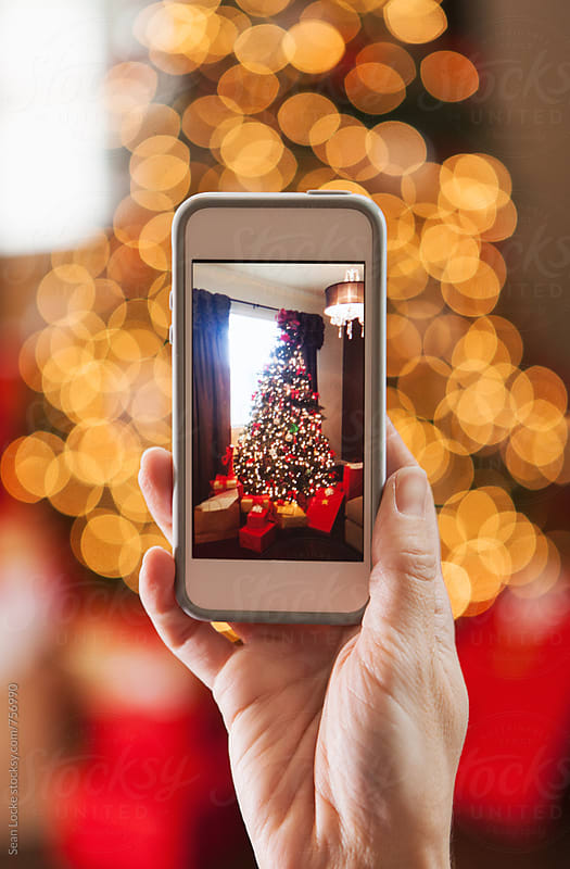 Christmas: Photographing Tree On A Cell Phone by Sean Locke for Stocksy United