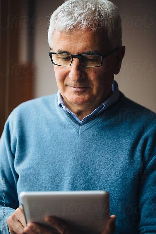 Portrait of a senior man using a digital tablet  by michela ravasio for Stocksy United