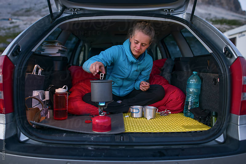 Woman cooking in the back of the car by RG&B Images for Stocksy United