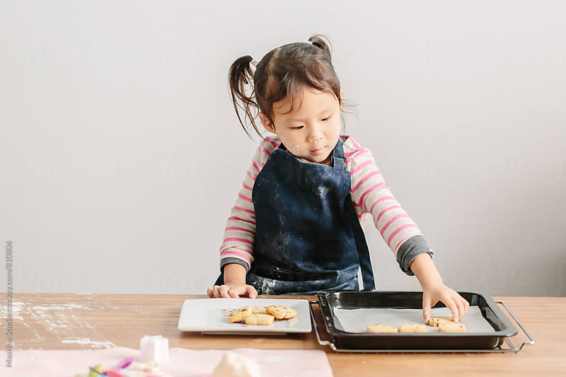 Toddler girl collecting baked cookies by MaaHoo Studio for Stocksy United